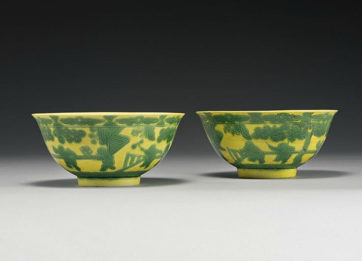A pair of yellow-ground green-enameled 'Boys' bowls, Yongzheng marks and period