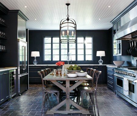 house and home dark black kitchen rustic farmhouse table beadboard ceiling stainless appliances pavers floor marble countertops