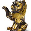 A rare small chinese gilt-bronze figure of a seated lion. northern wei-tang dynasty, 6th-7th century