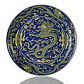An imperial yellow-glazed blue ground saucer dragon dish. Qianlong seal mark in underglaze blue and of the period