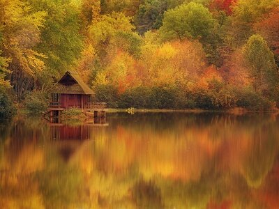 robert-llewellyn-wooden-cabin-on-lake-in-autumn