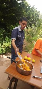 les morceaux coupés sont déversés par Ayoub dans la cocotte de cuisson