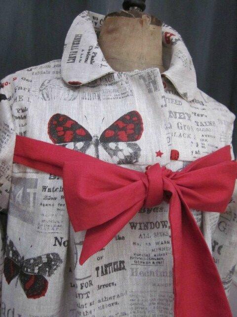 Manteau AGLAE en lin brut imprimé papillon rouge sur fond de journal fermé par un noeud de lin rouge (3)