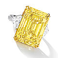 An impressive fancy vivid yellow diamond and diamond ring
