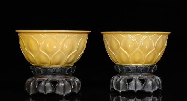 A fine pair of mustard yellow Beijing glass bowls on fine carved wood stands. China, engraved four-character Qianlong marks and of the period © 2010 Nagel