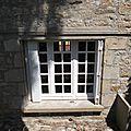 Remplacement d'une fenêtre par une baie sur une façade en pierres, habillage du linteau béton en pierre .