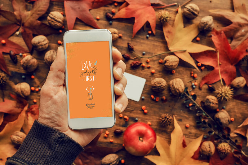 mock-up-smartphone-in-hand-with-autumn-decoration-AD6RXPM