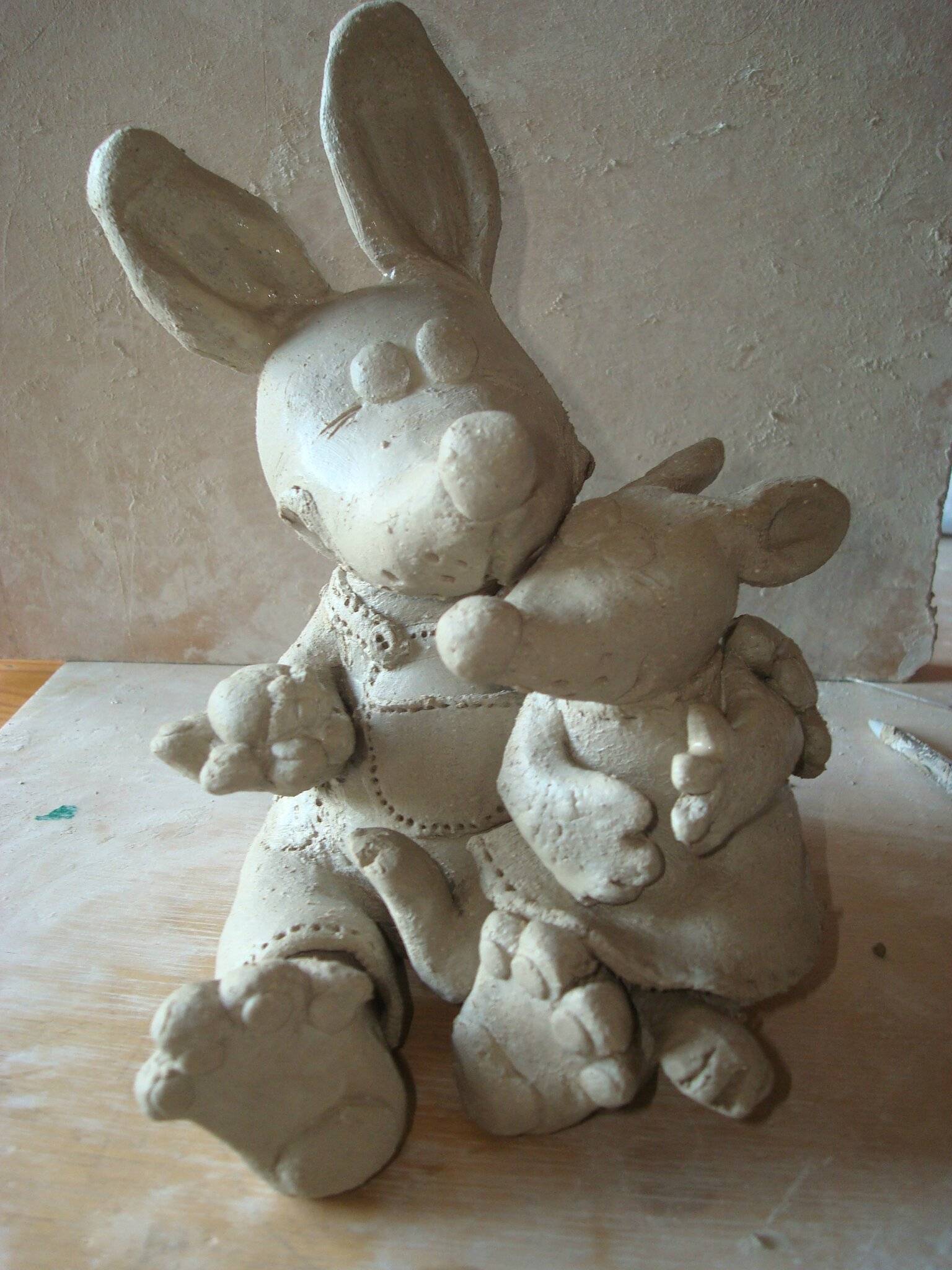 43) La petite lapine est assise sur une des jambes de son papa