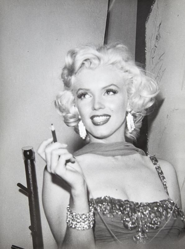 A black and white photograph of Marilyn Monroe in a jeweled gown preparing  to sign her signature 49ef3ace5