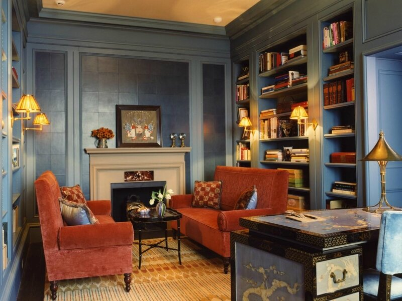 traditional-living-room-design-with-blue-painted-wooden-wall-library-shelves-and-fireplace-plus-oval-black-polished-metal-coffee-table-as-well-as-red-fabric-couch