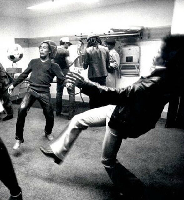 Bob Marley and Jimi Hendrix fooling around with a soccer ball backstage
