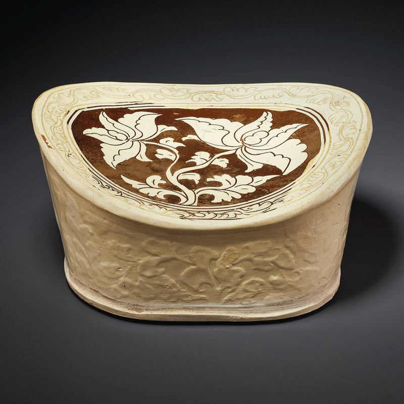 A Cizhou carved and molded cream-glazed pillow, Jin dynasty