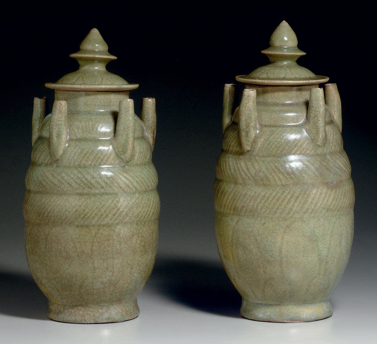 A pair of Zhejiang celadon carved five-spout jars and covers, Northern Song dynasty, 11th-12th century
