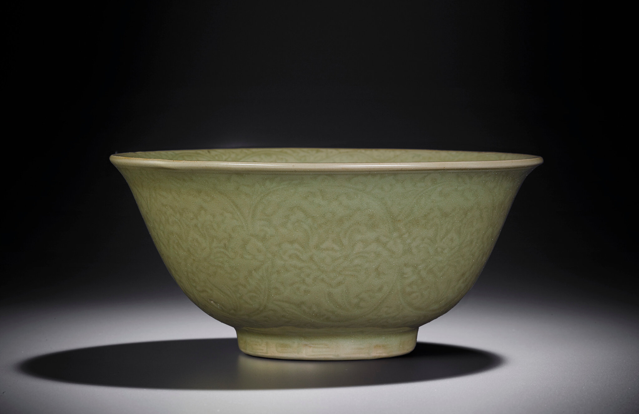 A rare carved Longquan celadon deep bowl, Yongle-Xuande period (1403-1435)