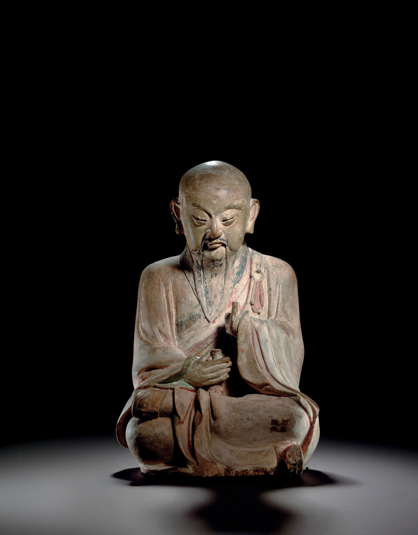 A painted stoneware figure of a seated luohan, Song-Ming dynasty, 12th-16th century