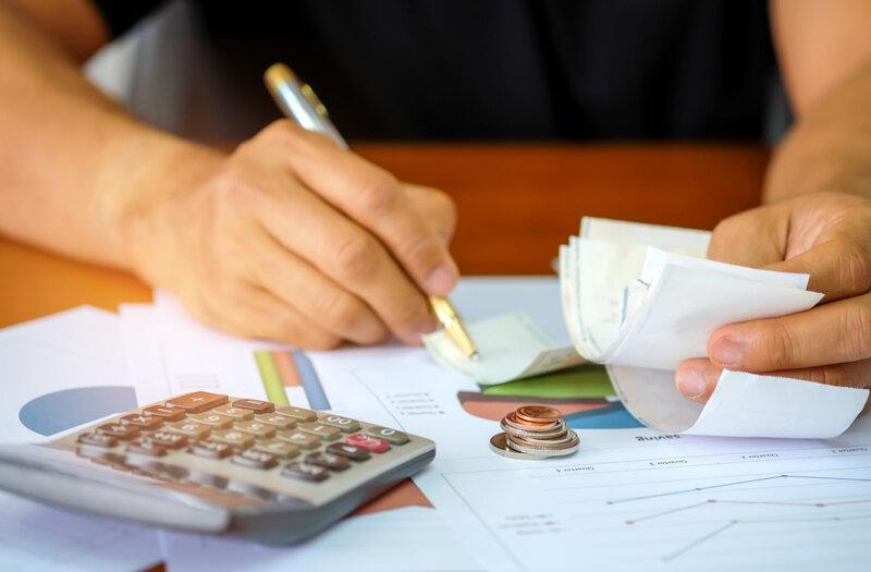 men-are-using-a-calculator-to-analyze-slip-credit-PFE6VF9-1600x1050