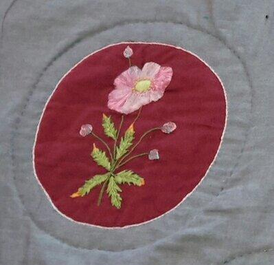 Anémone brodée sur du tissu fil à fil