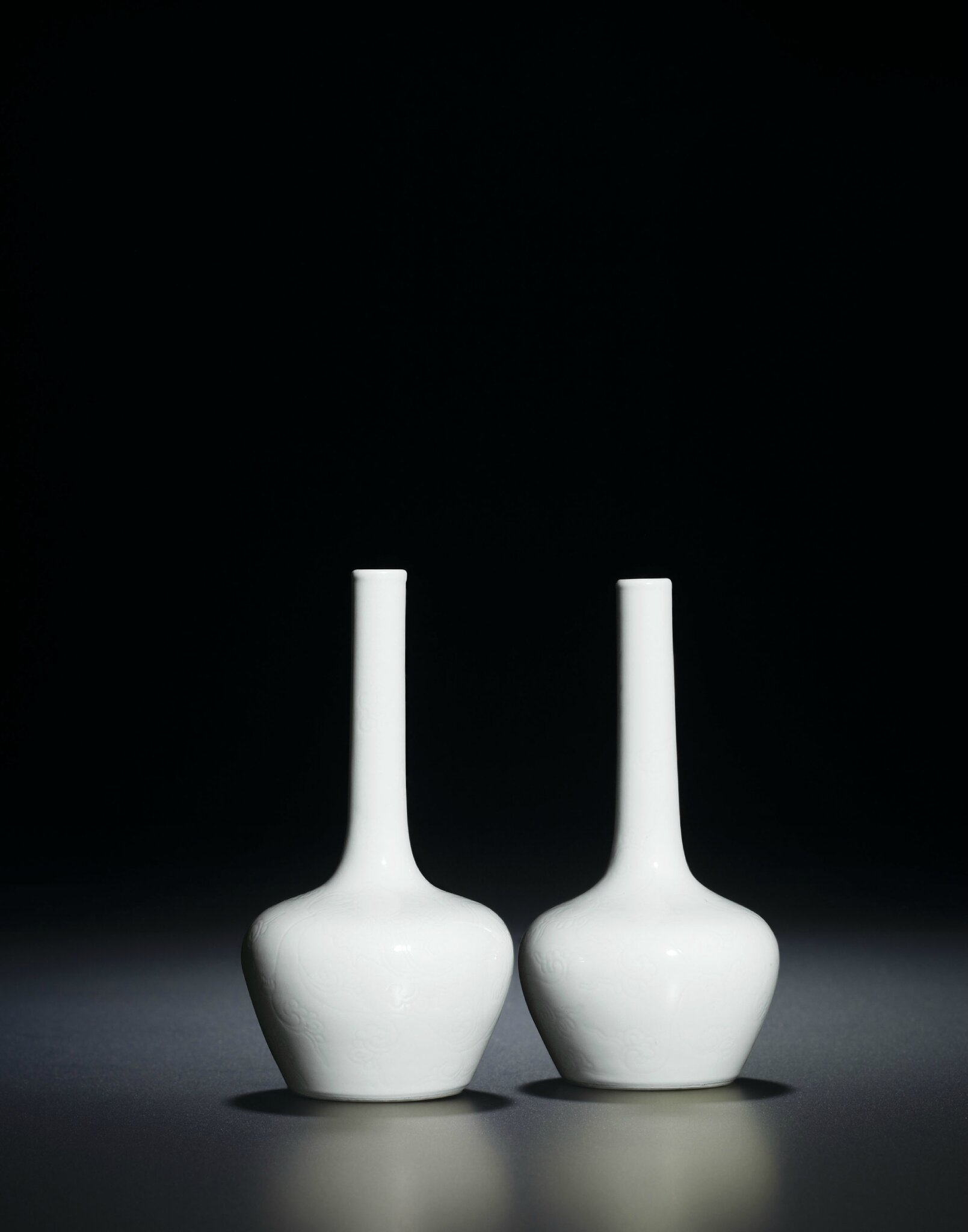 A fine and very rare pair of incised white-glazed bottle vases, Yongzheng six-character marks within double circles and of the period (1723-1735)