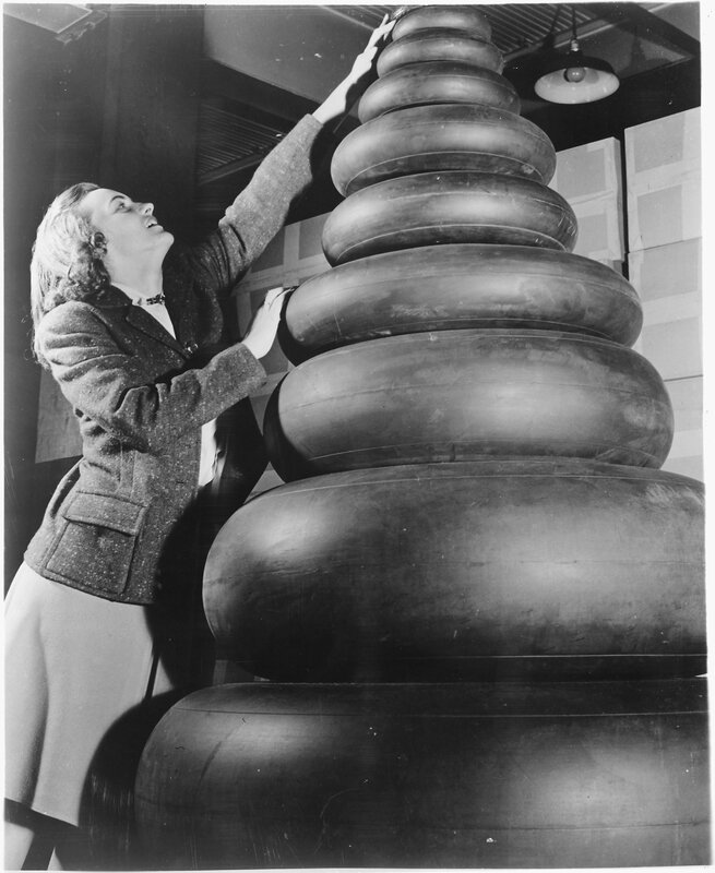 Woman_standing_next_to_a_wide_range_of_tire_sizes_required_by_military_aircraft