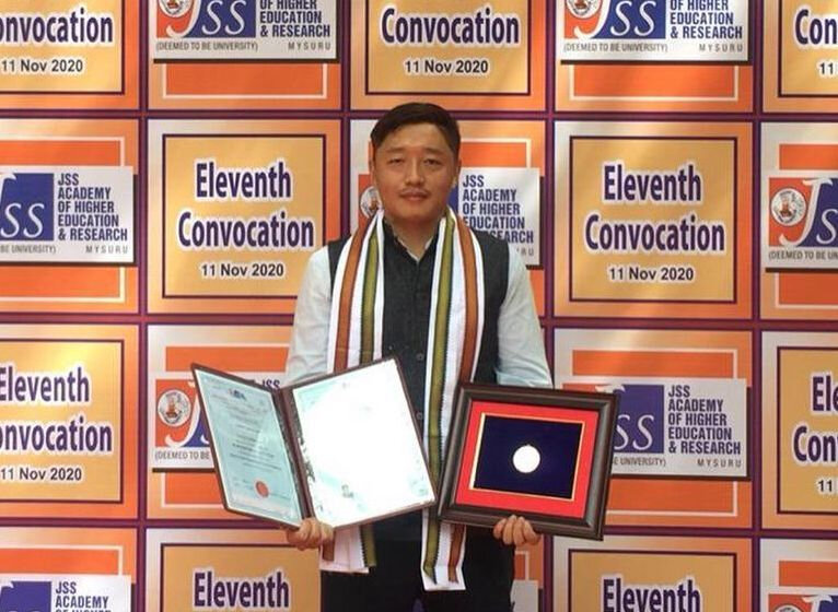 Pema-Gyaltsen-holding-the-medal-at-JJS-University-in-Mysore-Phayul-Photo