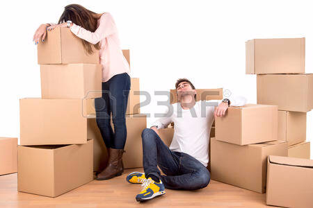 26408033-tired-couple-with-boxes-moving-into-new-home-apartment