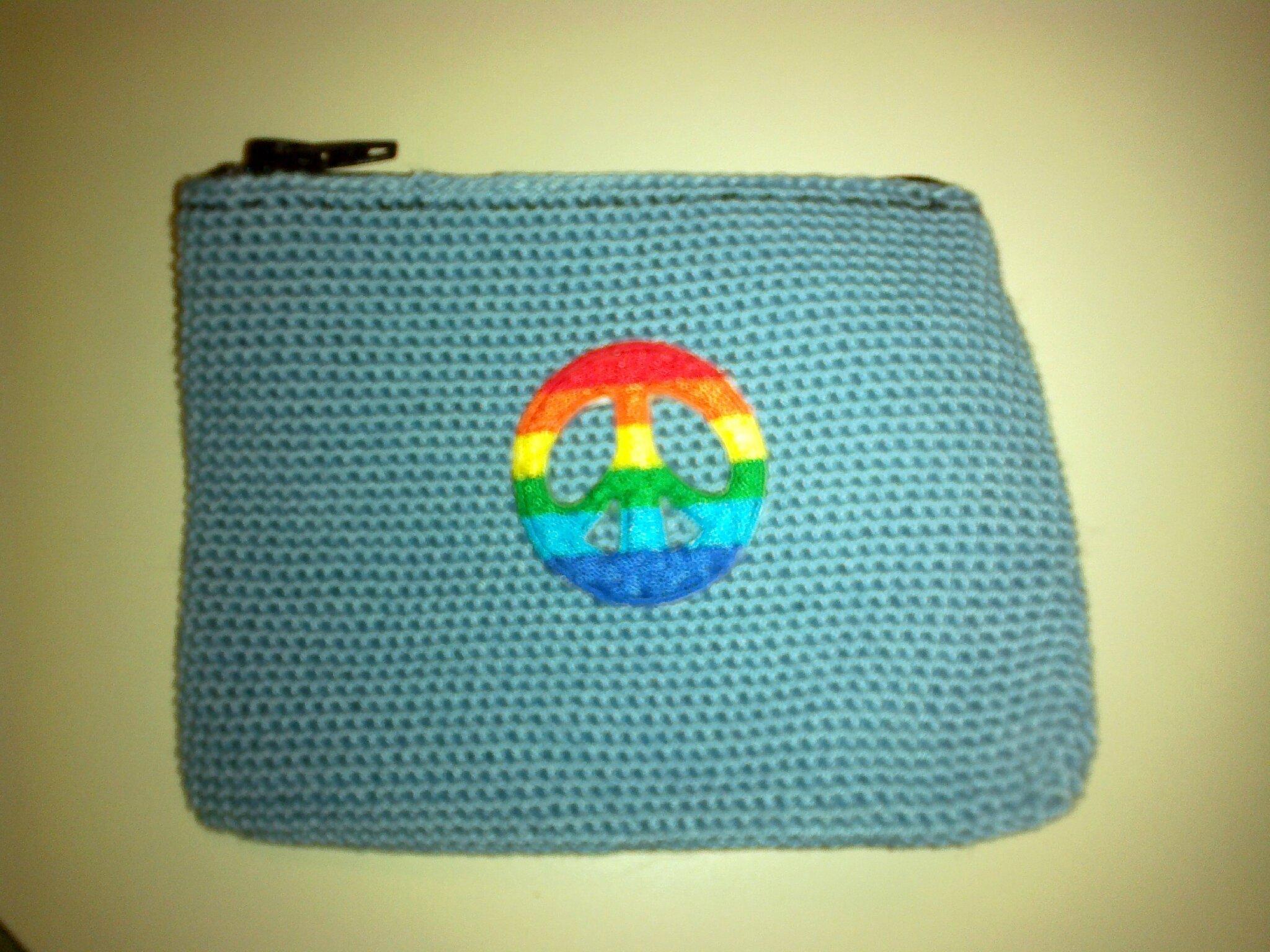 porte-monnaie crocheté bleu ciel avec écusson peace and love multicolre et fermeture éclair noire