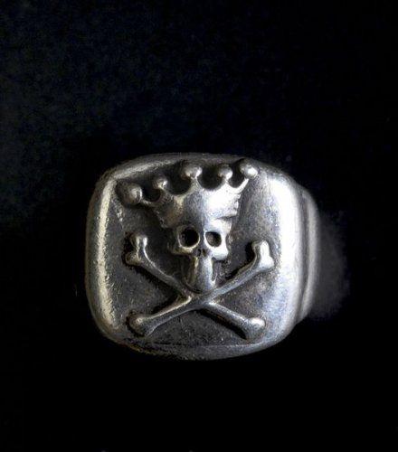 Bague en argent représentant un crâne couronné et tibias croisés.